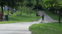 Cute boy, riding on scooters in the park, speeding toward the camera, summert Stock Footage