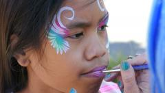 Face Painted Asian Girl Getting Purple Lips - stock footage