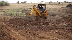 Bulldozer digging dry soil savanna, India, long shot Stock Footage