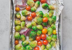 Closeup portrait of oven baked and spiced vegetables in pan lined by aluminum - stock photo
