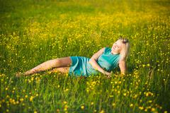 Young  business woman laying on grass outside after hard work in office. Kuvituskuvat