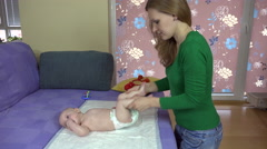 Mother massage and exercise little baby daughter legs on bed. 4K Stock Footage