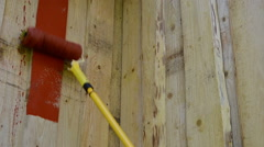 Closeup of roller brush paint wooden plank house wall Stock Footage