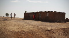 2 men walk next to poor village house in drought dry area, India, long shot Stock Footage