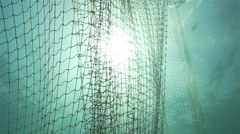 The sun penetrates into the water and illuminates the spectacular fishing net Stock Footage