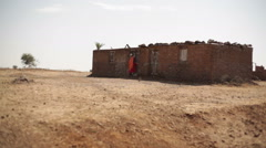 Woman fixing door in poor village house in drought dry area, India, long shot Stock Footage