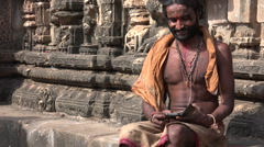 Indian guru uses smartphone, contrast between traditional versus modern - stock footage