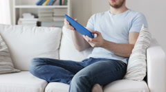 Close up of man playing game on tablet pc at home Stock Footage