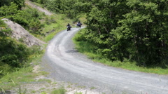 Group of motorcyclists driving on dirt road in the woods Stock Footage