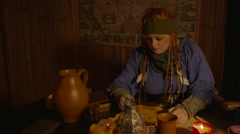 Female Pirate reading a map on a table with candles Stock Footage
