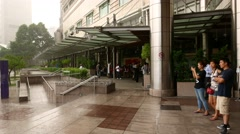 People hiding from showers at mall entrance canopy, rainy KLCC park panorama Stock Footage