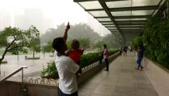 People hiding from the rain but enjoy the weather and view, KLCC park Stock Footage