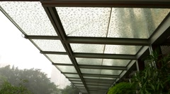 Raindrops on glass visor roof, ornate with leaf image. View from bottom on Stock Footage