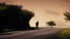 Cyclist Rides Up Hill At Sunset With Car Passing Stock Footage