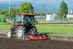 Tractor Tilling a Rice Field Stock Photos