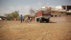 Boys play cricket in India village, long shot, shallow DOF Stock Footage