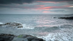 Waves crashing off a rocky shoreline at Sunset Stock Footage