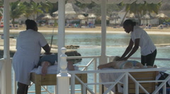 Jamaican women massaging on the beach in Jamaica - stock footage