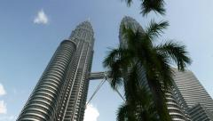 Looking up to Menara Petronas, right tower closed by palm trees, dolly shot Stock Footage
