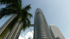 Dolly panning shot Petronas Twin Towers from ground level Stock Footage