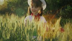 A little girl among green wheat ears 2 Stock Footage