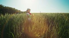 A little girl among green wheat ears 1 Stock Footage