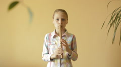 Little girl plays flute Stock Footage
