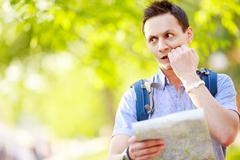 Young man with a map outdoors - stock photo