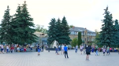 Adults and children rest in the square near the fountain Stock Footage