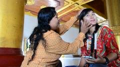 Burmese woman using thanaka makeup for traveler Stock Footage