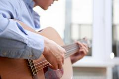 Man playing classic, acoustic guitar Kuvituskuvat