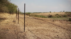 Old rusty barbed wire fence on a dry farm, medium shot, shallow DOF Stock Footage