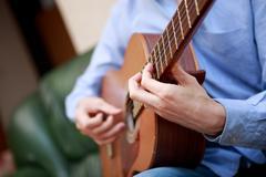 Man playing classic, acoustic guitar Stock Photos
