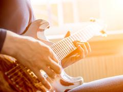 Male hand playing on acoustic guitar. Close-up - stock photo