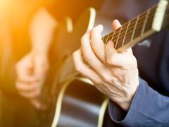 Male hand playing on acoustic guitar. Close-up Stock Photos