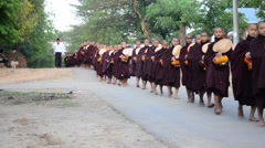 Monk procession walking on the road for people pray and put food offerings Stock Footage