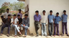 Group of Indian village teen boys hanging around, long shot, shallow DOF Stock Footage
