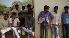 Group of Indian village teen boys hanging around, medium shot, shallow DOF Stock Footage