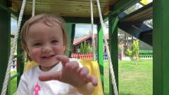 Happy Little girl on swing reaching at camera. UHD 4K steadycam stock footage Stock Footage