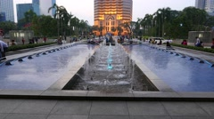 Menara Public Bank building, twilight, KLCC, panning up from fountain view Stock Footage