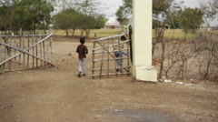 Small village boys hit cricket ball and enter gate, India, long shot Stock Footage