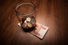 Bundle of bank notes and a glass jar with coins - stock photo