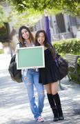 Excited Mixed Race Female Students Holding Blank Chalkboard Stock Photos