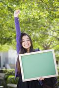 Excited Mixed Race Female Student Holding Blank Chalkboard - stock photo