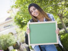 Excited Mixed Race Female Student Holding Blank Chalkboard Stock Photos