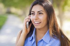 Smiling Mixed Race Young Adult Woman Using Her Cell Phone Outside. - stock photo