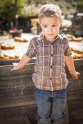 Little Boy Standing Against Old Wood Wagon at Pumpkin Patch. - stock photo