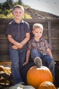 Two Young Boys at the Pumpkin Patch Leaning Against Antique Wood Wagon. - stock photo