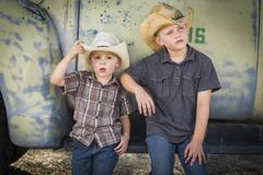 Two Young Boys Wearing Cowboy Hats Leaning Against Antique Truck. - stock photo