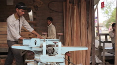 Man and boy working in a sawmill, child labor India, long shot Stock Footage